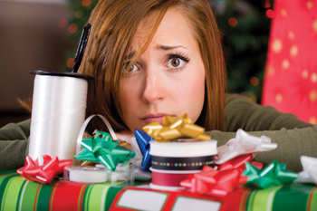 stressed out mom wrapping Christmas presents; overwhelmed by holidays