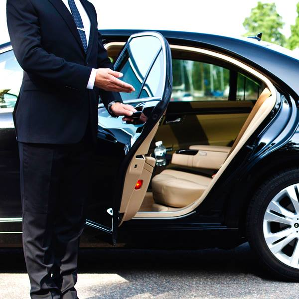 A chaffeur opening the door of a Carmel Car & Limousine Service vehicle.