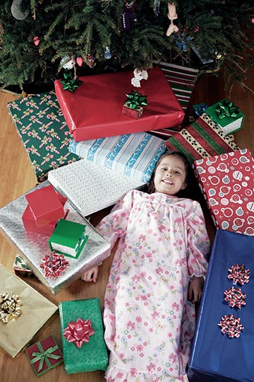 girl surrounded by presents on christmas