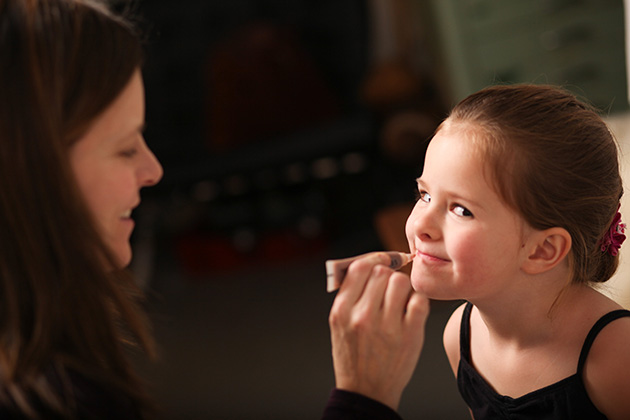 mother applying lip gloss on daughter