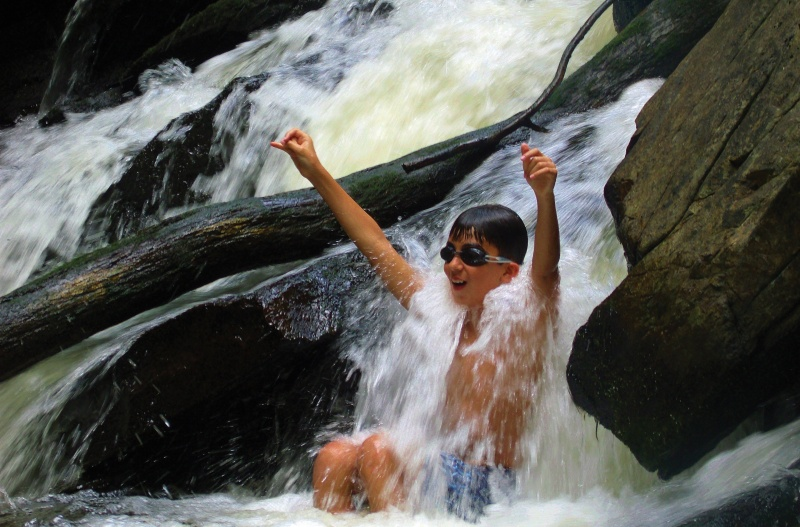 child playing in waterfall