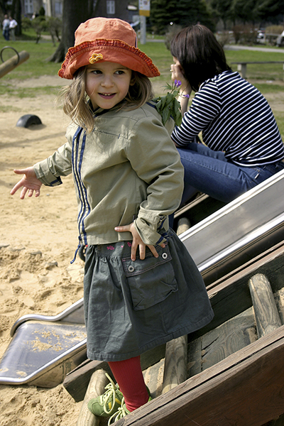child on playground with nanny in background