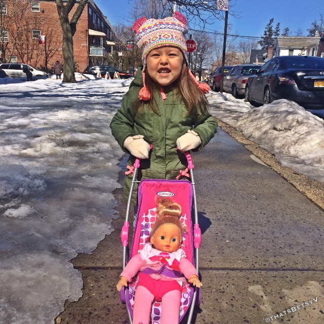 young girl pushing doll in stroller