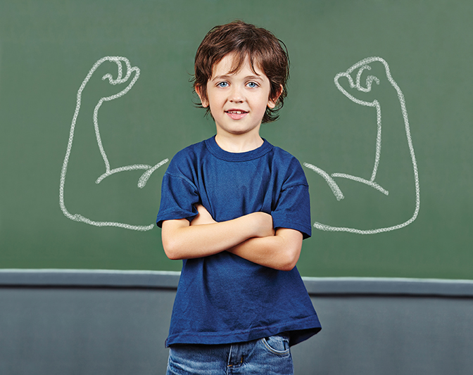boy in front of blackboard with muscles