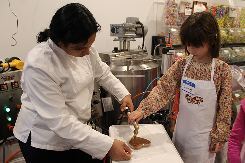girl pouring chocolate into a mold at chocolate works