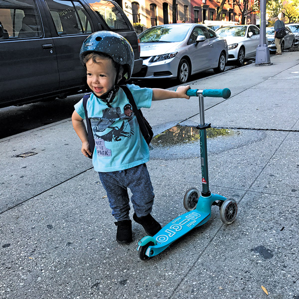 smiling boy riding scooter