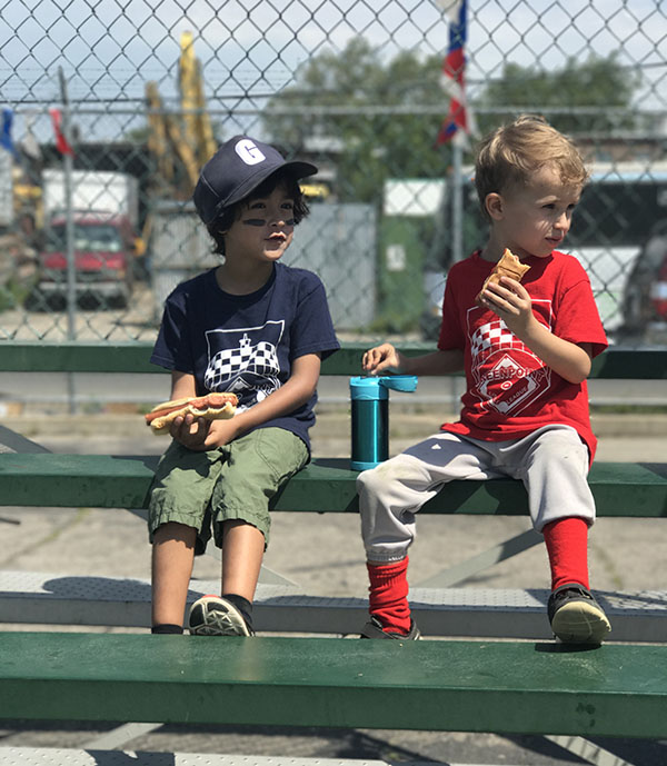 two young kids on bench at baseball field