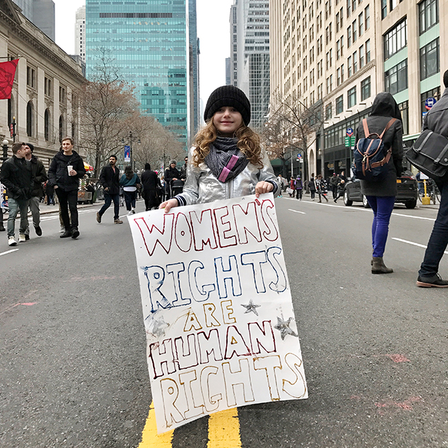 girl holding protest sign