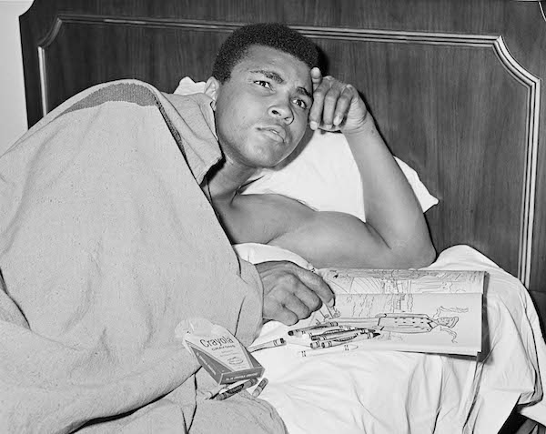 Ali with coloring book of military officers, 1967