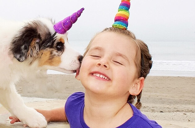 young girl with puppy wearing unicorn horns