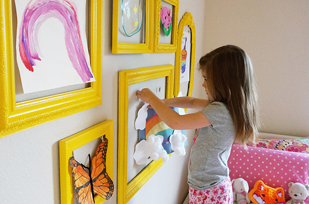 young girl hanging art in frames on wall