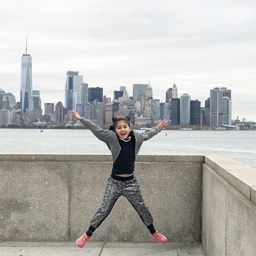 young girl jumping nyc skyline