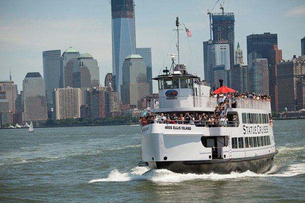A Statue Cruise in front of the Manhattan skyline.
