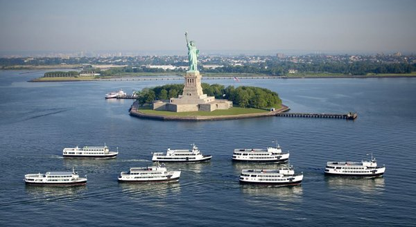 A small group of Statue Cruises surrounding the Statue of Liberty.