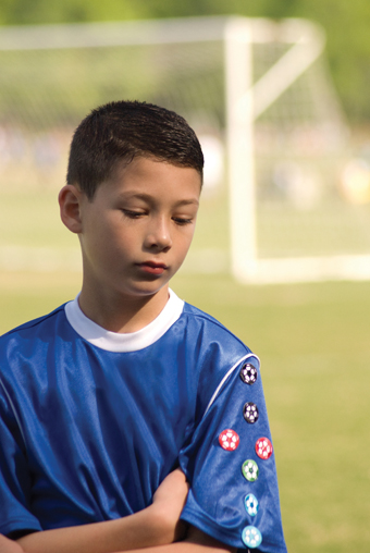 sad boy on soccer field