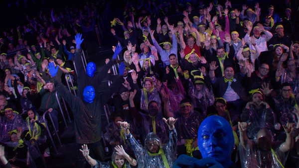 An audience being covered in paint during a Blue Man Group performance.