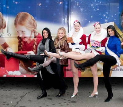 Crystal Bowersox and Miss USA Rima Fakih pose with a few Radio City Rockettes in front of the CitySights NY tour bus; Holiday Joy Toy Drive