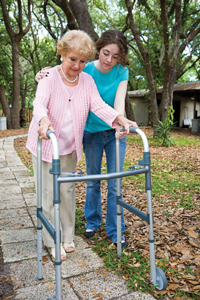 young girl helping elderly woman with walker