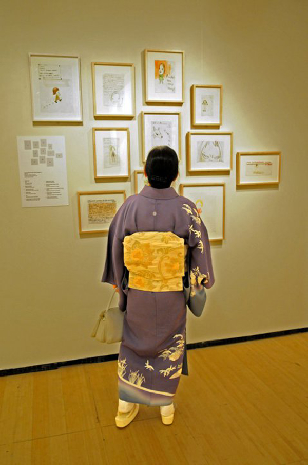 A visitor examining works of art on display at the Asia Society and Museum.