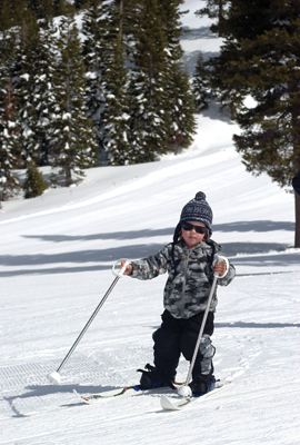 little boy skiing in sunglasses