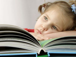 Sad little girl with book