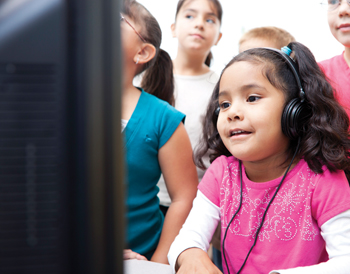 children learning by computer; little girl with headphones; learning disability