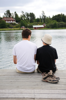 boy and camp counselor sitting by the lake at summer camp; camp pemigewasset