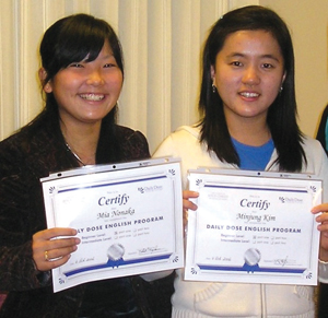 Students Mia Nonaka from Japan and Minjung Kim from Korea hold up their ESL certificates