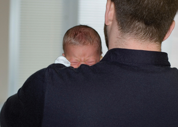 nervous new dad; father holding crying newborn