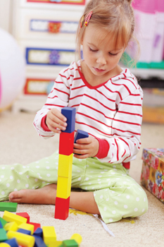 little girl playing with blocks; special needs child