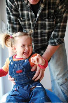 father holding happy toddler girl; kids gyms