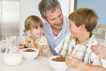 happy family; dad and two small children eating breakfast at the table together
