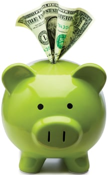 green piggy bank with dollar bill sticking out; piggy bank full of money; saving money