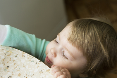 toddler reaching up onto table; small girl reaching for something on top of table