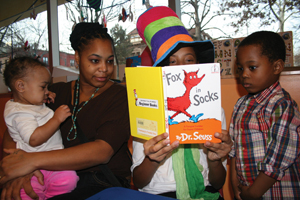 Family reading Dr. Seuss book at Brooklyn Chlldren's Museum; Reading Fox in Socks by Dr. Seuss