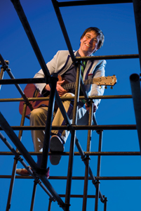 Justin Roberts on jungle gym, with guitar