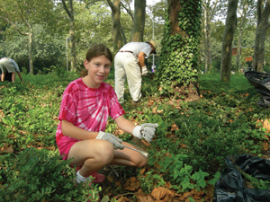 park volunteer; young girl helping clean up a park