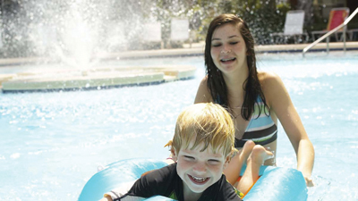kids playing in the pool; family vacation; sister and brother in pool