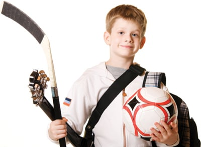 boy holding sports, music, and school equipment; well rounded child