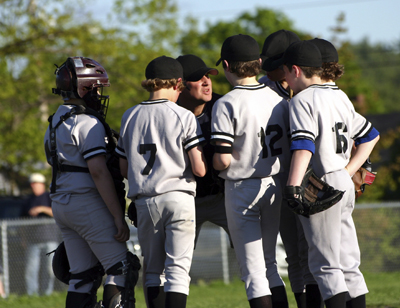 little league team in huddle with coach