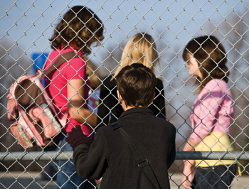 child on outside of playground looking in; kids separated by a fence