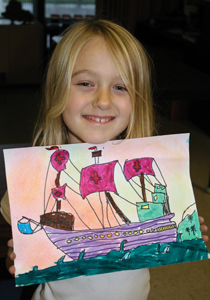 little girl holding her artwork; kids art class