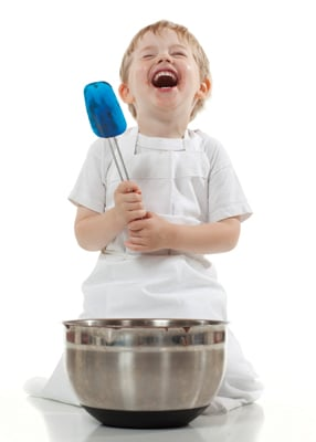 child laughing while holding spatula, baking brownies; kid cooking in kitchen