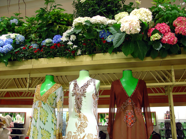 Three designer dresses on display inside of Macy's Herald Square.