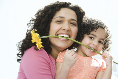 mom and daughter holding a flower
