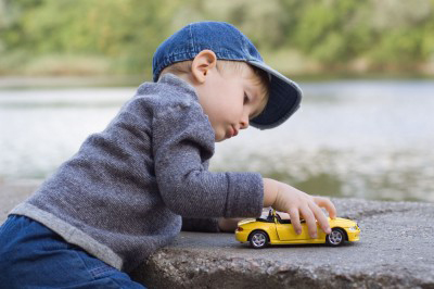 young boy playing with a toy car outside