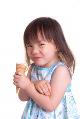 little girl in summer dress eating ice cream cone