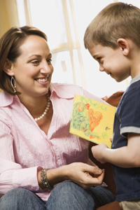 little boy giving mom a Mother's Day card