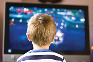 child glued to the TV; little boy watching television