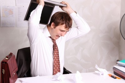 stressed man with laptop at work